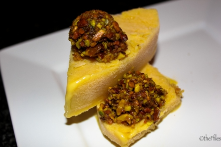 Photo of a sweet mango kulfi (frozen treat from the Indian Sub-continent), topped with a slightly crunchy, slightly salty pistachio haroseth.